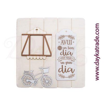"""Tabla rectangular con tablero, bici y ventana con mensaje en catalán """"Avui es un bon dia per tenir un gran dia""""."""