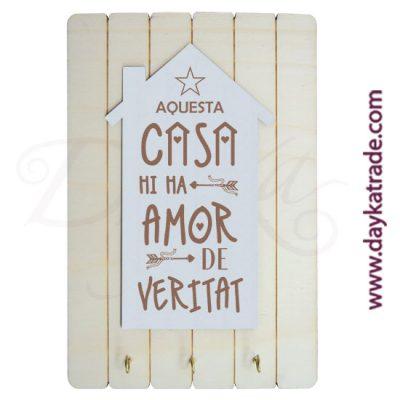 """Cuelga llaves con tabla rectangular con tablero con mensaje en catalán """"Aquesta casa mi ma amor de veritat""""."""