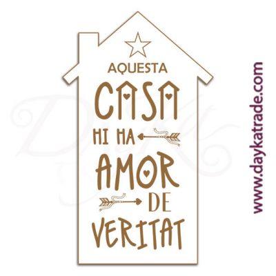 """Etiqueta de tablero lacado blanco con mensaje grabado """"Aquesta casa mi ma amor""""."""