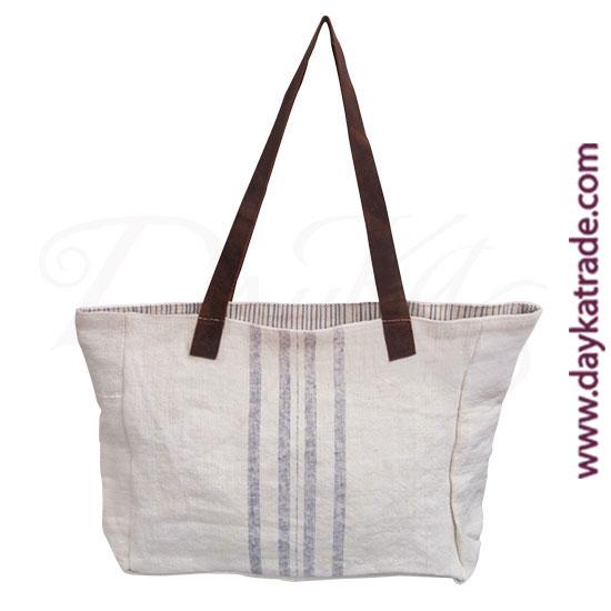 Bolso de hombro de tela color crema con lineas verticales de color lila y asa de piel