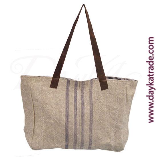 Bolso de hombro de tela color yute con lineas verticales de color lila y asa de piel